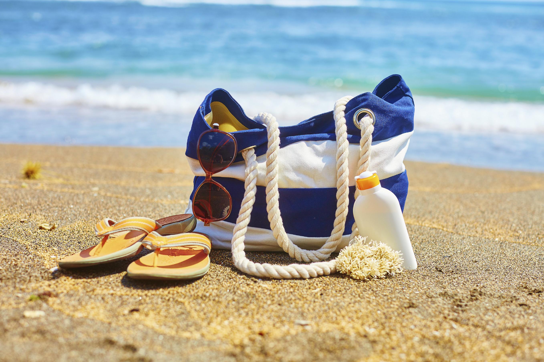 Beach bag, flip flops, and sunscreen bottle