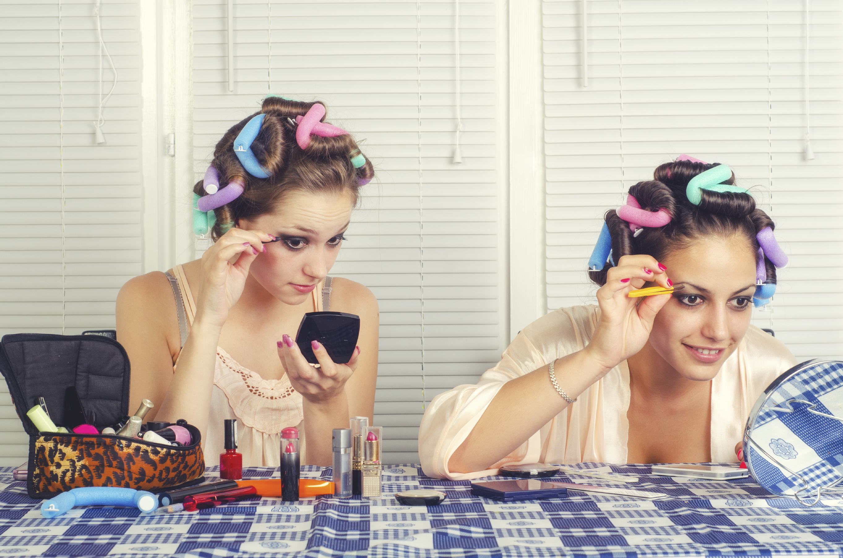 Two young housewives beautifying themselves at home