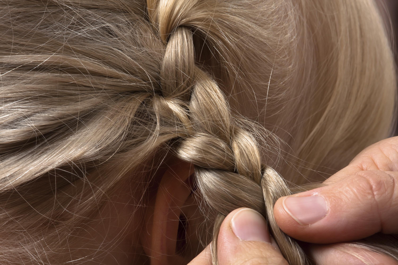 hands of hairdresser weaving braid